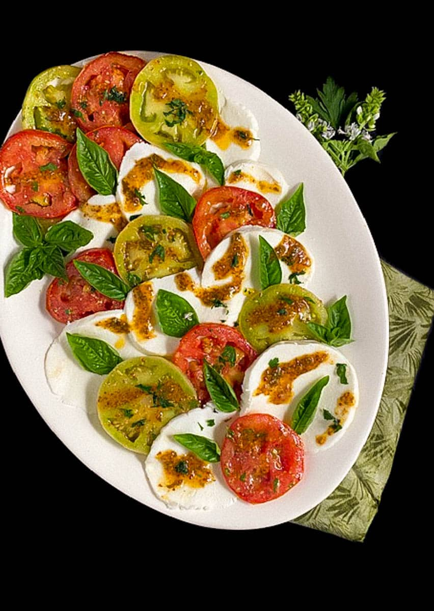 Creole Caprese Salad on an oval white plate against a black background.