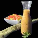 A clear dressing jar filled with Creole mustard Vinaigrette with a parsley leaf and salad against a black background.