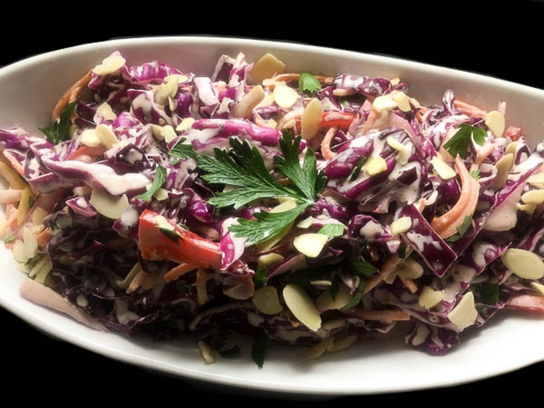 A white oblong bowl filled with Rainbow Red Cabbage Coleslaw against a black background.