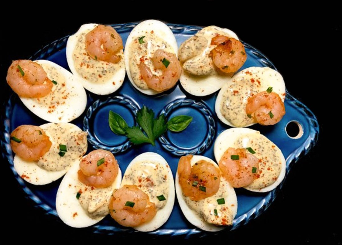An oval blue serving plate filled with Creole Shrimp Stuffed Eggs.