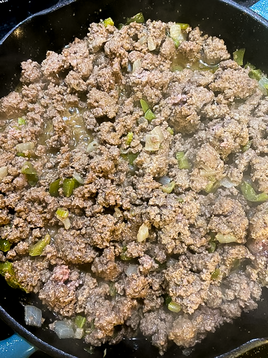 Browned ground beef and veggies in a skillet.