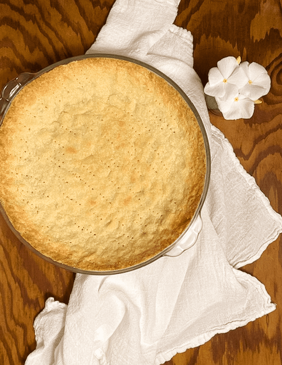 4-ingredient almond flour pie crust against a brown background with white flowers.