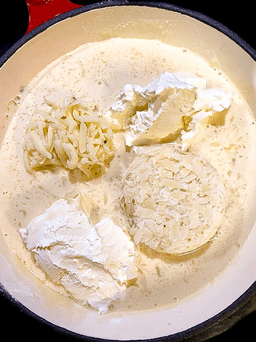 Three cheeses melting into milk in a cast iron skillet.