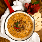 A red enameled cast iron skillet filled with fresh Gluten Free Baked Cajun French Onion Dip