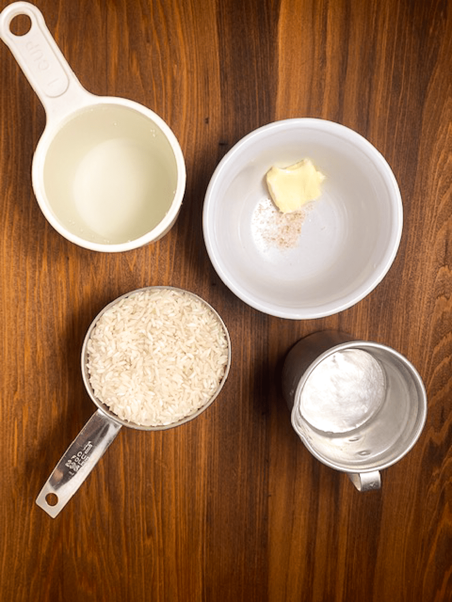 Uncooked rice, water, butter and salt against a brown background.