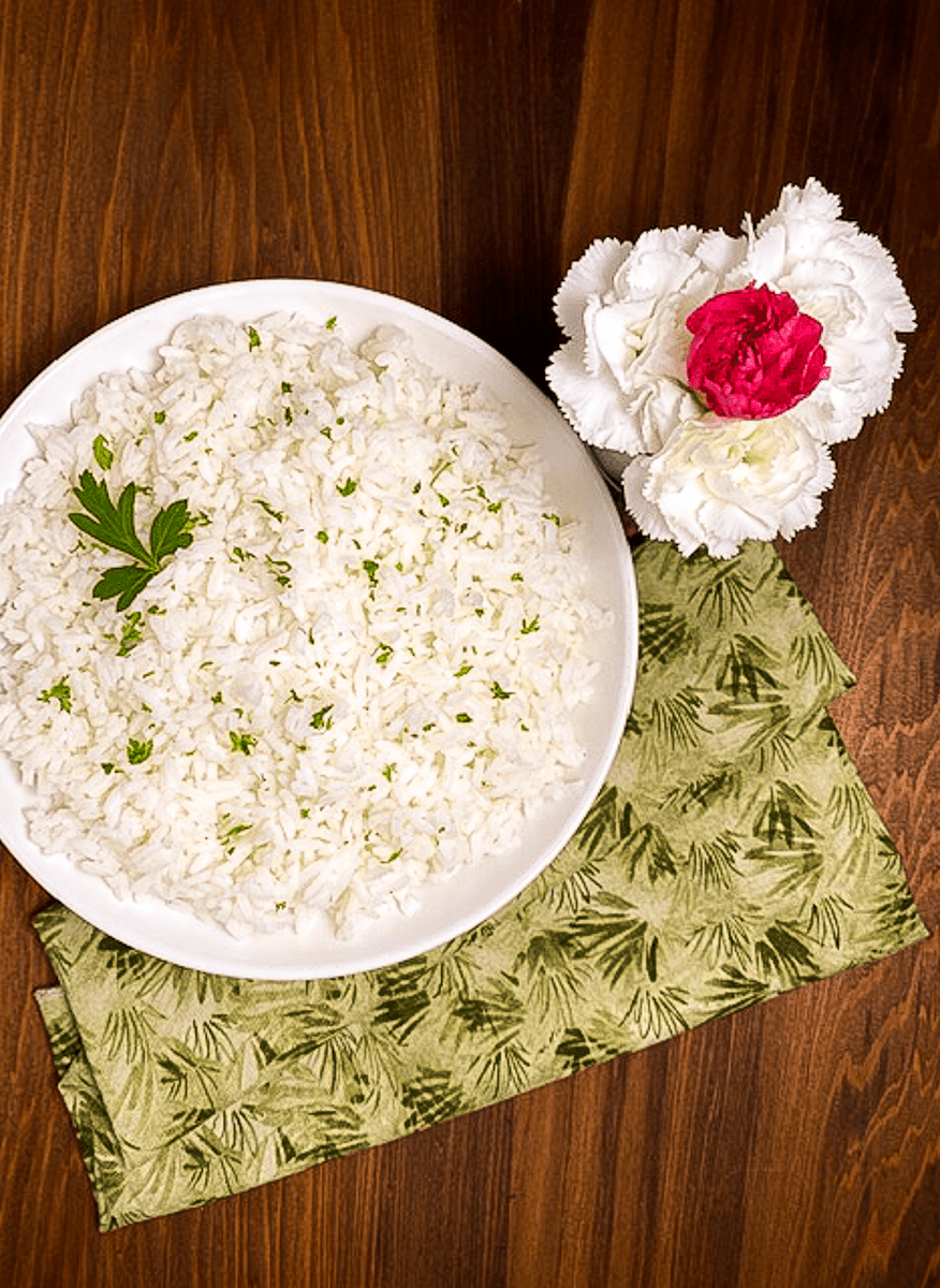 A bowl of perfect white rice with flowers against a brown background