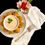 A round white plate filled with Cajun Crab Balls {Grain or Gluten Free} and homemade remoulade sauce against a black background with flowers.