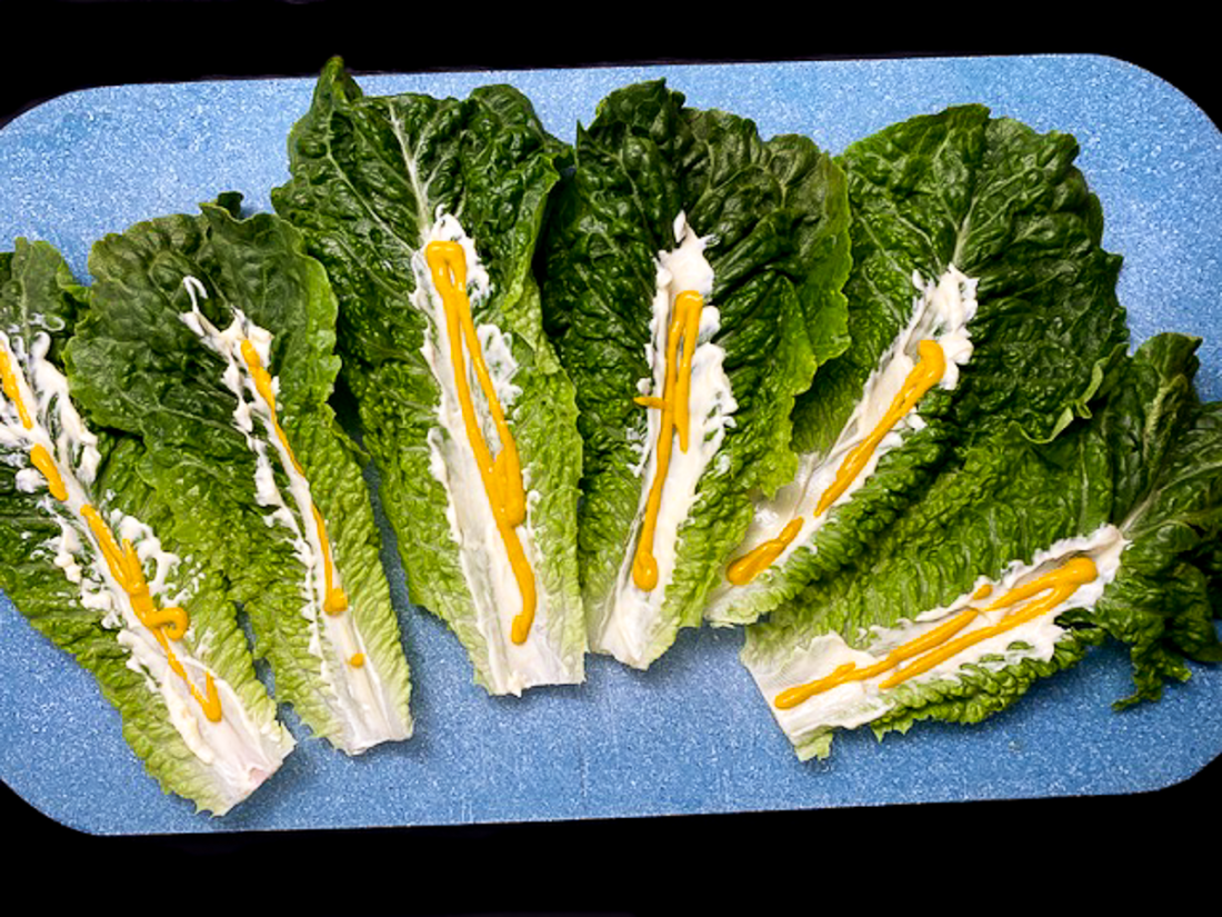 Romaine lettuce leaves dressed with mayonnaise and mustard.