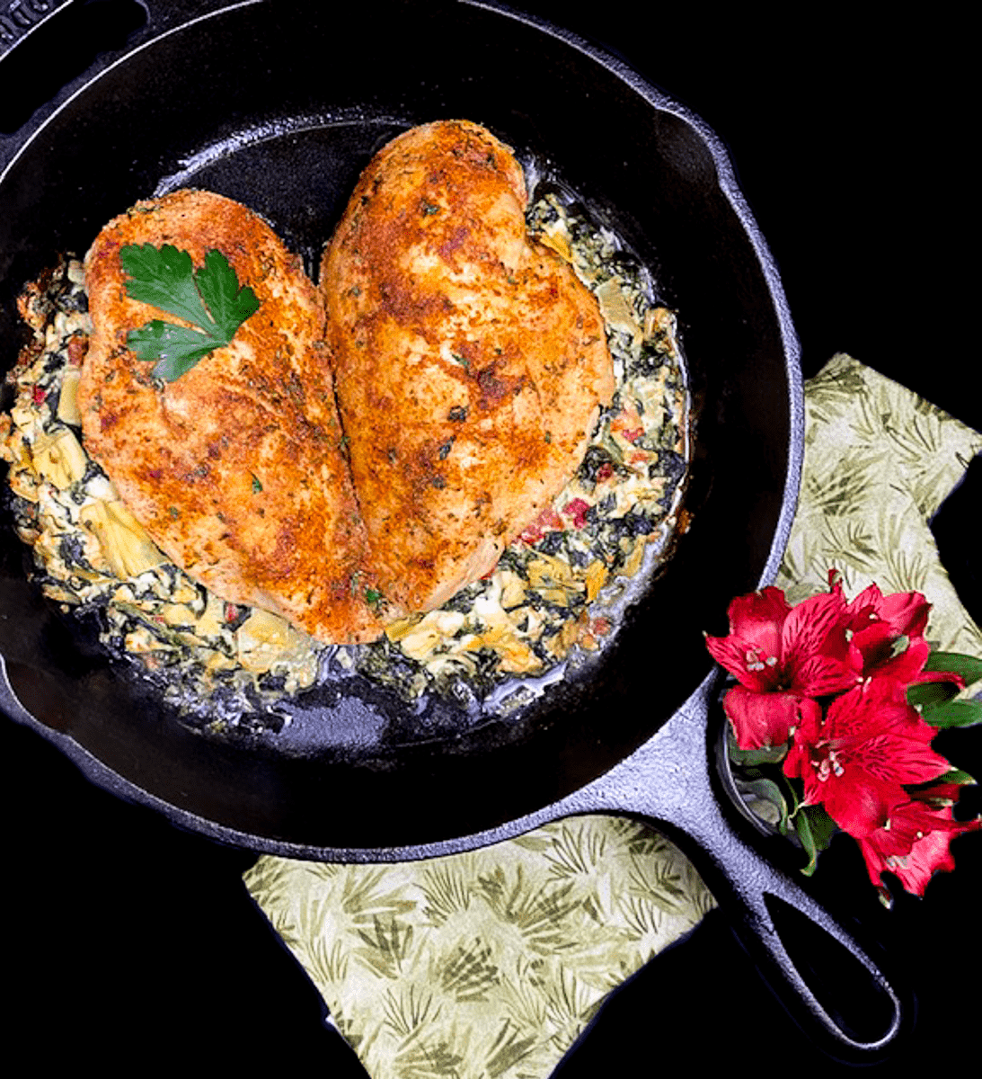 A black cast iron skillet filled with Cheesy Spinach & Artichoke Stuffed Chicken Breast {Keto, Low Carb, Grain & Gluten Free}