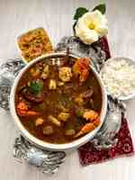 A round white bowl filled with Grain Free & Gluten Free Creole Gumbo with cooked rice and cauliflower rice against a white backdrop.
