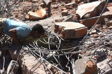 Seorang warga mengintip dibalik reruntuhan rumah yang rusak akibat gempa bumi saat proses evakuasi korban di rumah tersebut di Pemenang, Lombok Utara, NTB, Selasa (7/8). Berdasarkan data BNPB mencatat sedikitnya 98 korban meninggal dunia akibat bencana gempa bumi yang terjadi Minggu (5/8) dan kemungkinan masih akan bertambah.
