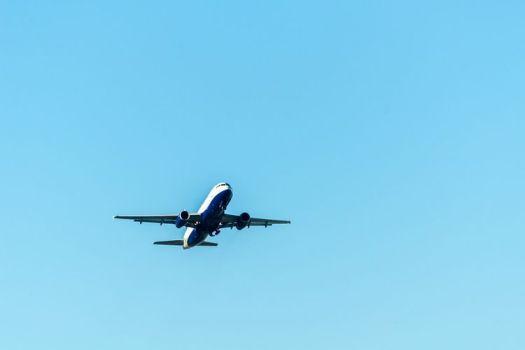Pesawat terbang komersial melintas di udara.