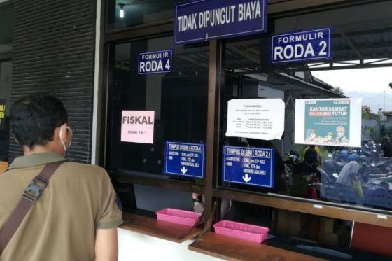 Wajib Pajak menunggu berkas di depan loket fiskal di kantor Samsat di Solo