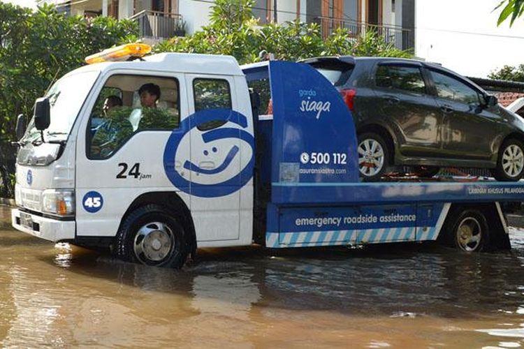 Mobil pelanggan diselamatkan oleh perusahaan Asuransi akibat banjir di Ibukota, Senin-Selasa (9-10/2/2015).