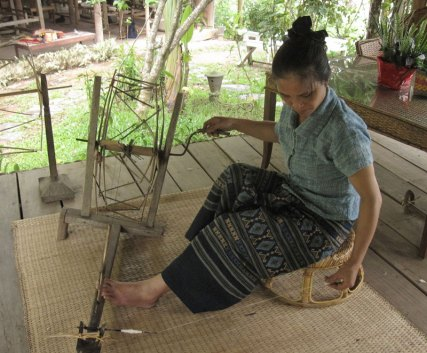 Ock Pop Tok artisan, Euay Navon, spins organic cotton on a traditional wheel. (photo credit: Tracy Hudson)