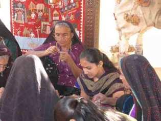 The Kala Raksha group stitches together.
