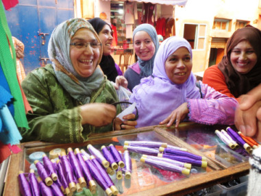 Moroccan women buying thread at market.