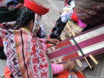 A weaver from Chaullacocha, Peru, demonstrates her traditional-style pictorial weaving on a backstrap loom. Note the beaded hat band.