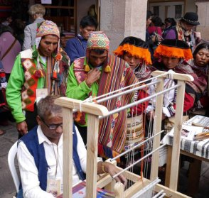 Sallac village weavers watch Dayabhai weave on a foot-pedal floor loom.