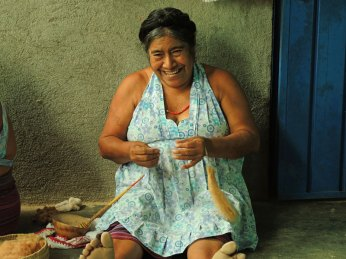 Feliza spinning brown cotton using the traditional handspindle and gourd bowl.