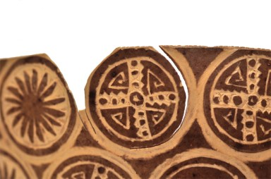 Detail of a button being removed from gourd edge.
