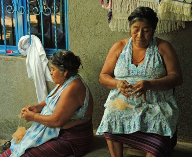 Paula (left) and Feliza (right) prepare the brown cotton (coyuche) for spinning.