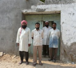 Abdul Jabbar Mohammed Khatri (left) stands next to his son. He and other family are traditional Ajrakh block printers.
