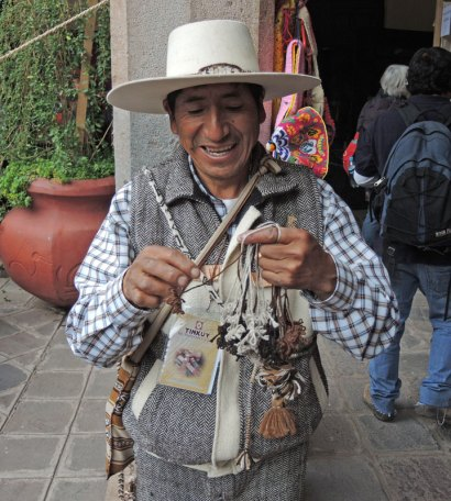 Traditional sling-braid maker from Arequipa, Peru, forming a multi-stranded braid in his hands.