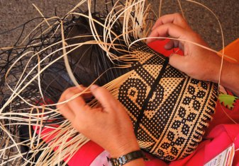 The woven design in process using natural and naturally-dyed rattan.