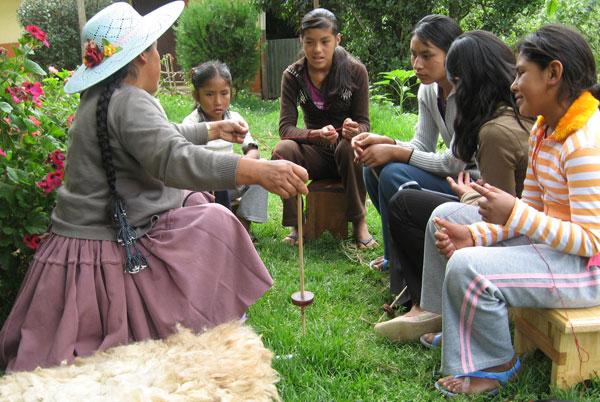 Doña Màxima Cortez, trainer for Club de Artesanas and Warmis Phuskadoras team captain, teaching chicas to spin.
