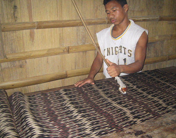 The final cloth is ironed with a cowrie shell to bring out the luster.