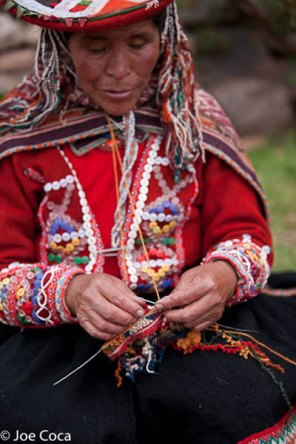 """An elder has just started knitting a """"popcorn"""" hat. Strings of grutas are ready to be inserted into the knit hat."""