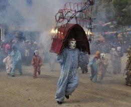 Zinacantan clowns racing through plaza with fireworks.