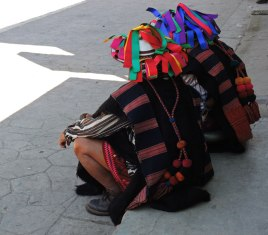 Colorful ribbons adorn the woven hats. The handwoven vest has brocading at the bottom edges.
