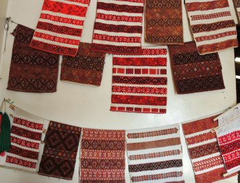 The wall of the coop store is covered with the distinctive red-and-black brocade patterned cloths as well as naturally dyed ones.