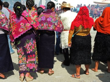 The stark contrast of the floral dress of Zinacatecs and the wooly-skirted women of Chamula.