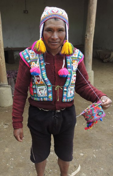 "Knitting the multi-colored hat. His vest is as colorful as the hat. The hearts on the vest say ""LUVE""."