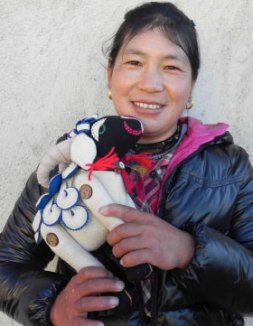 Yondron holds one of the Tibetan sheep she has made.