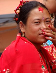 A married Nepali woman wearing red sari, vermillion hair stripe, and tika dot (red nails too.)
