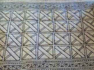 Large design blocks are drawn and then filled in with more detailed patterns. The lines are wax resist.