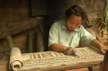 A young batik artist waxing an intricate pattern on hemp cloth. Photo credit: Ock Pop Tok