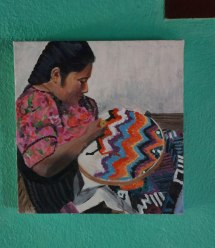 A painting of rug hooking in process hangs on the wall at Multicolores.