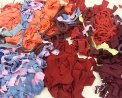 After careful color selection, the used clothing is cut into thin strips.