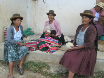 Doñas Felicidad, Justina, and Toribia wait to measure their handspuns in 2015.
