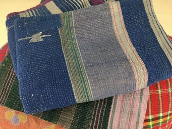 Stacks of kantha textiles.