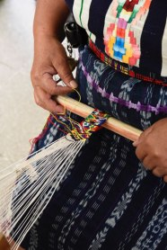 Emilia weaves a fine tapestry pattern. Note three other types of weaving she wears: a jaspe corte, a faja (belt), and a huipil with a colorful randa embroidered pattern.