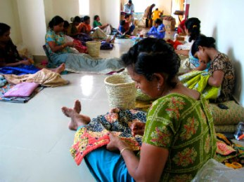 Women of the kantha stitching group work on the Red Sari collection.