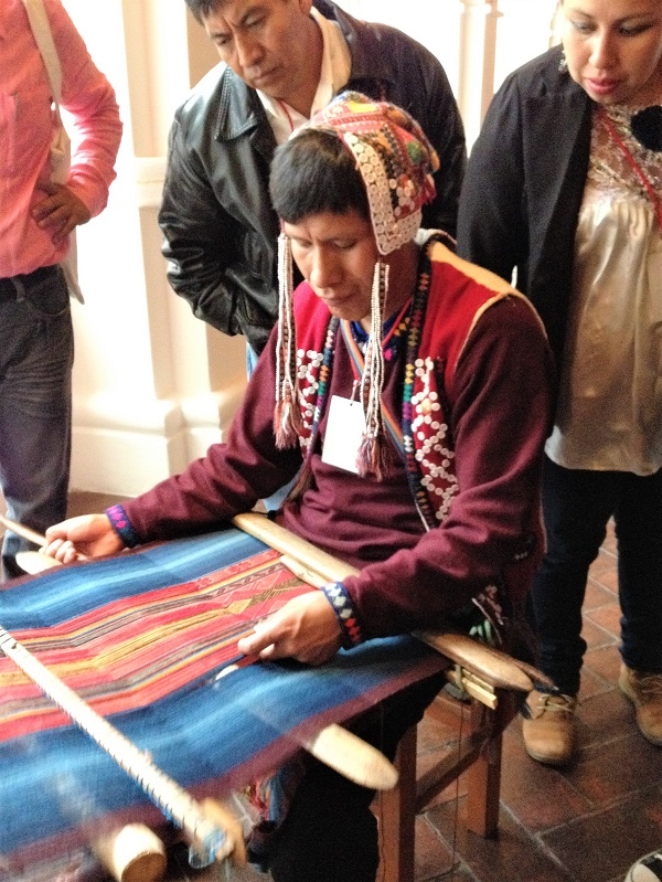 A young weaver demonstrating Peruvian backstrap weaving in Oaxaca.