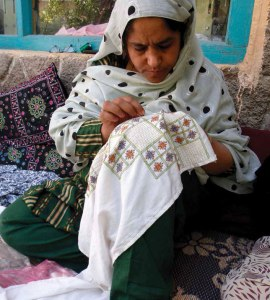 Paindo, a Kandahar Treasure embroiderer with fine creative skills, works on an original design. Photo credit: Mary Littrell