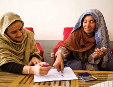 Rangina Hamidi (on left) records the payment to a Kandahar Treasure embroiderer. Her thumbprint is as good as a signature. Photo credit ©Paula Lerner/Aurora Photos.
